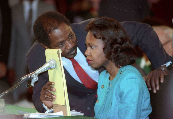 Counsel Charles Ogeltree uses a legal pad to cover a microphone as he advises law professor Anita Hill during her testimony O