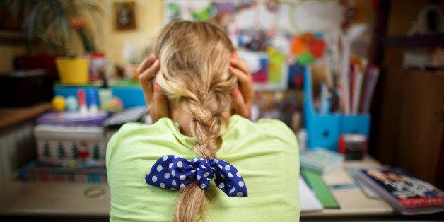 BONN, Germany - August 10: Eleven years old girl sitting at adesk doing her homework on August 10, 2015 in Bonn, Germany. (Ph