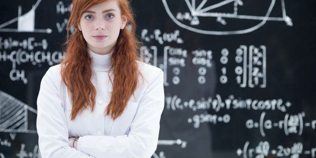 close-up of schoolgirl succesful looking  in the camera in a chemistry lab with a blackboard on the background