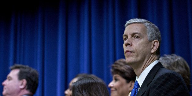 Arne Duncan, U.S. secretary of education, right, listens as U.S. President Barack Obama, not pictured, speaks before signing