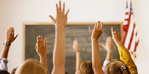 Students raising hands in classroom, rear view
