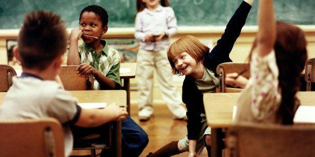 Children (6-8) in classroom, girls sitting at desk raising hands