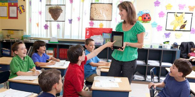 teacher using ipad / tablet to teach kids in class