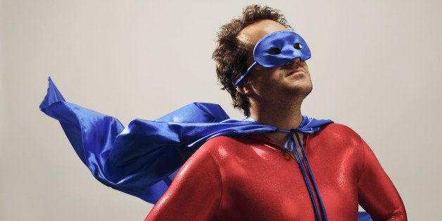Man wearing superhero costume, looking up