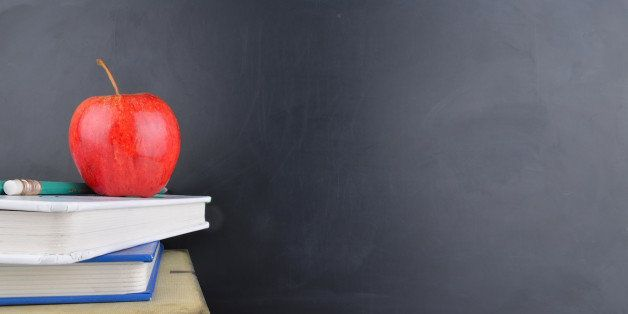 A classroom with a red apple, books and a blackboard with handwriting in white chalk on the board.