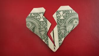 A broken origami dollar heart, on red