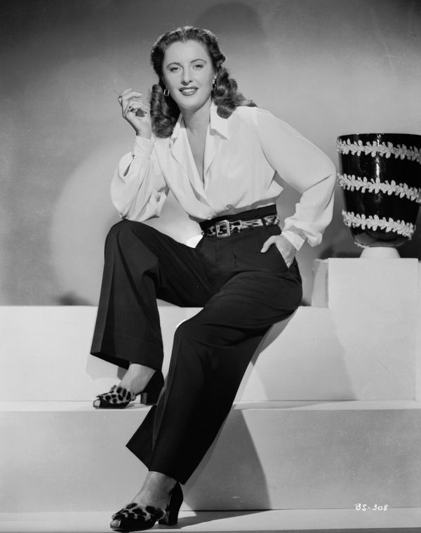 Stanwyck poses in a white shirt and black pants in this photo from 1945.