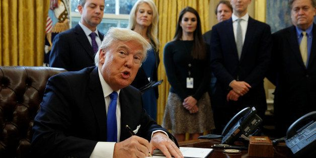 U.S. President Donald Trump looks up while signing an executive order to advance construction of the Keystone XL pipeline at
