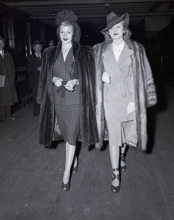 Actors Hayworth and Dietrich wear similar coats as they depart for Hollywood after a visit in New York in 1941.