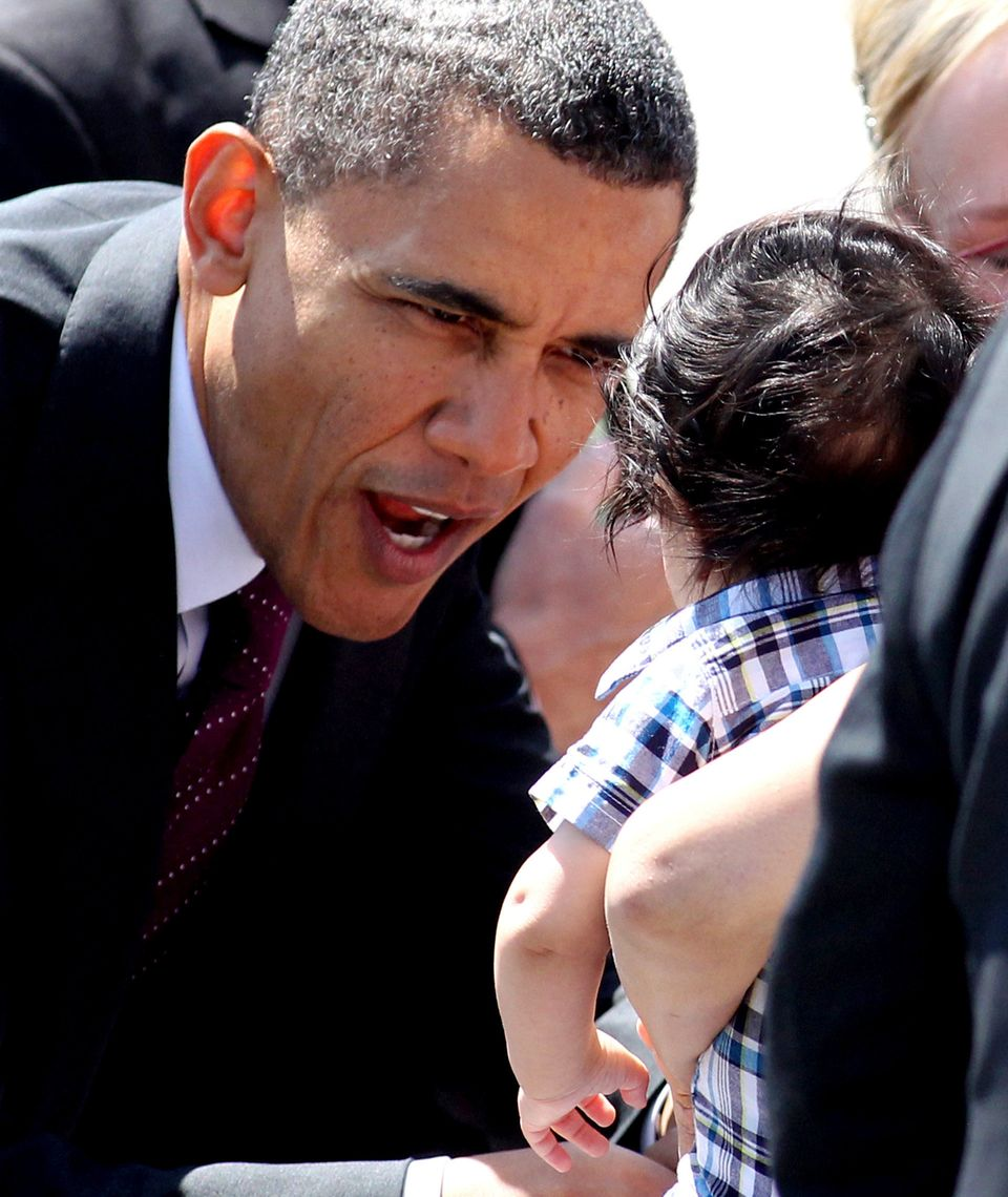President Barack Obama greets a baby in the crowd at the Reno-Tahoe International Airport in Reno, Nev., Friday, May 11, 2012