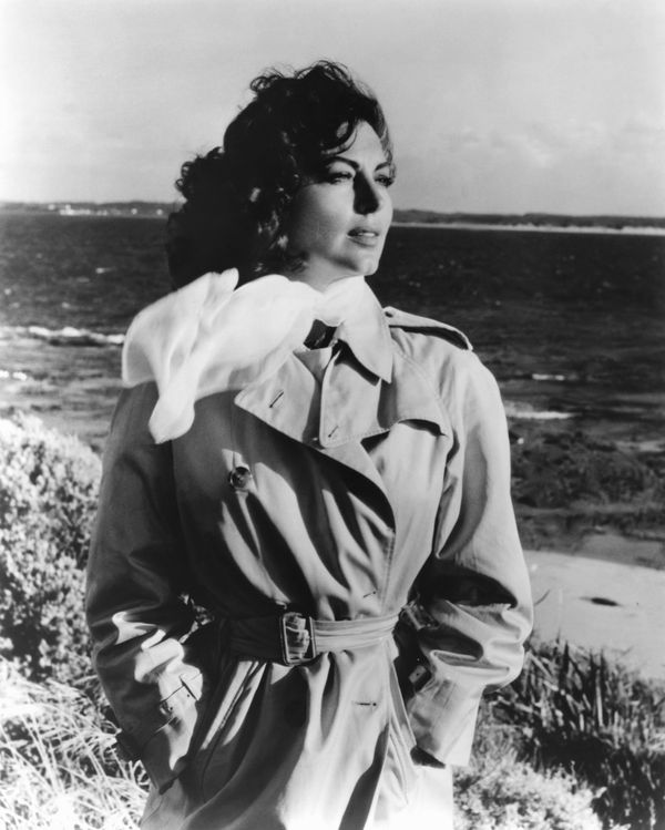 "Gardner in a trench coat and scarf on the set of the 1959 film ""On the Beach."""