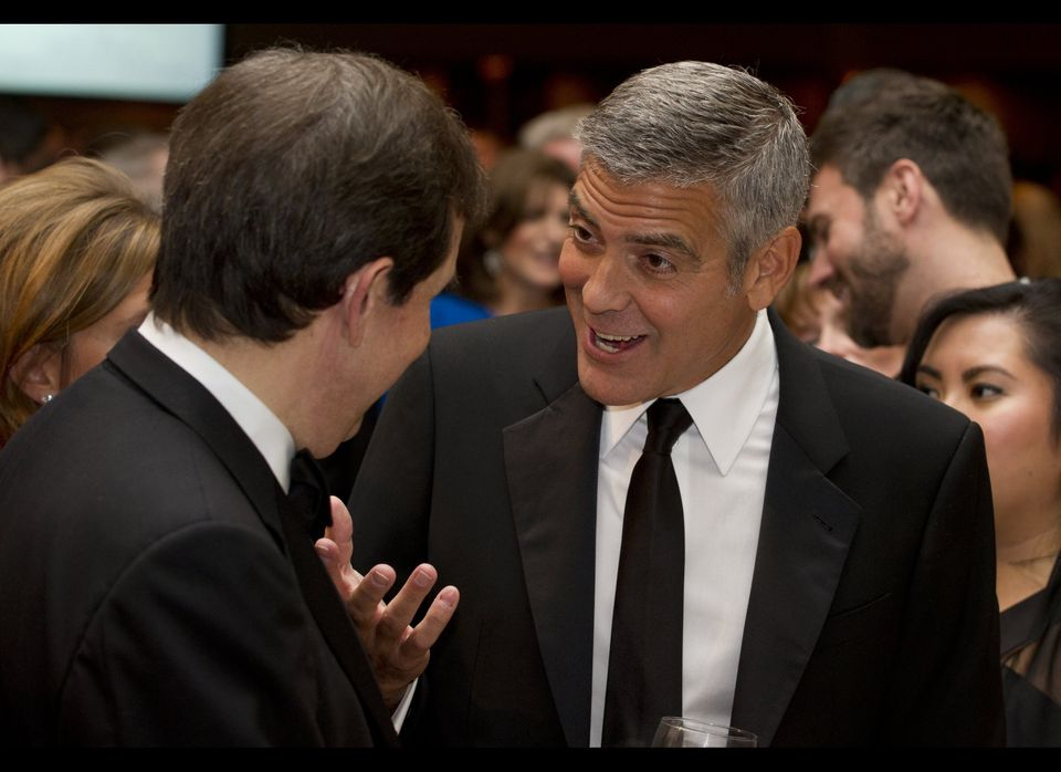Actor George Clooney speaks with Chris Wallace of Fox News as they attend the White House Correspondents Association Dinner i