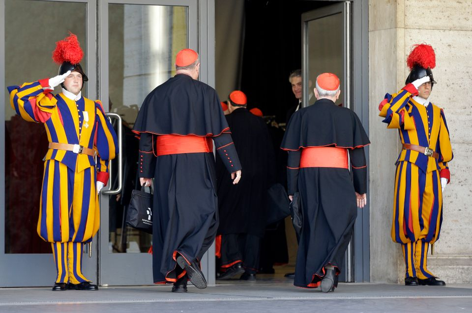 Vatican Swiss guards salute as cardinals arrive for a meeting, at the Vatican, Monday, March 4, 2013. Cardinals from around t
