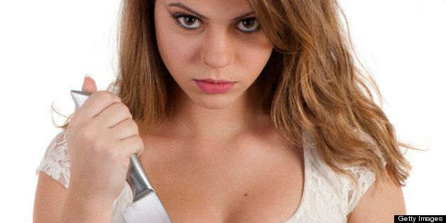 Beautiful blonde girl with an angry expression holding a knife