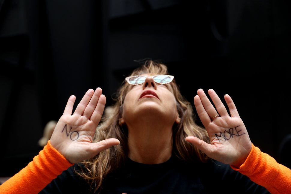 A protester displays a note on her hand that reads 'No More' while demonstrating.