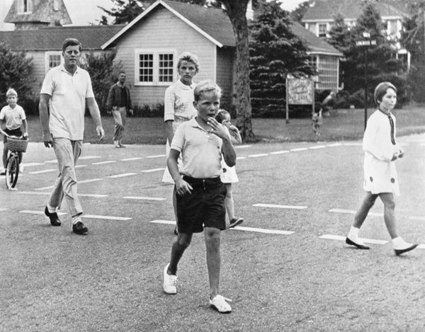 John F. Kennedy with some of the Kennedy children walk up the street to a nearby store to buy candy while vacationing in Hyan