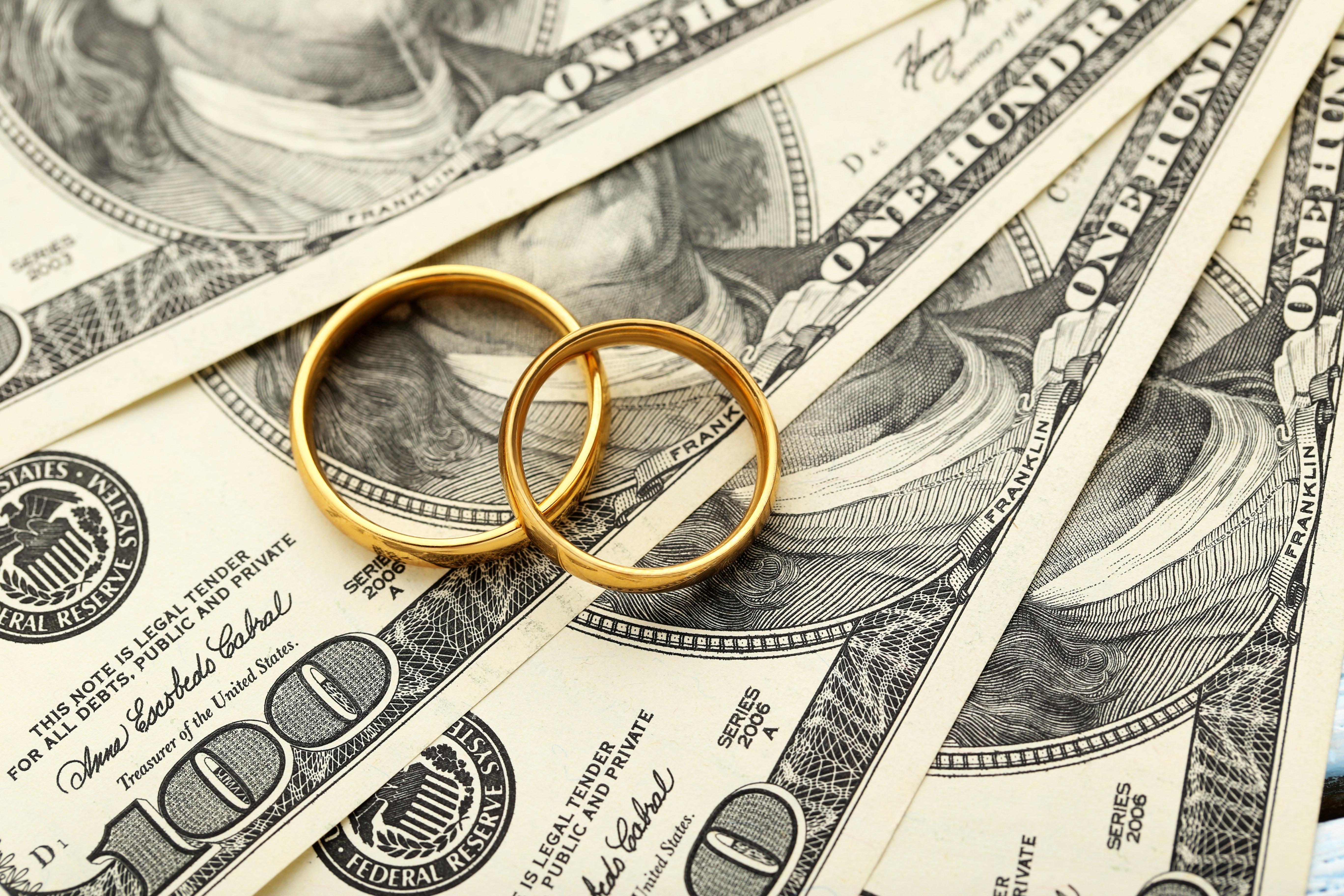 Golden wedding rings on one hundred dollars bill background