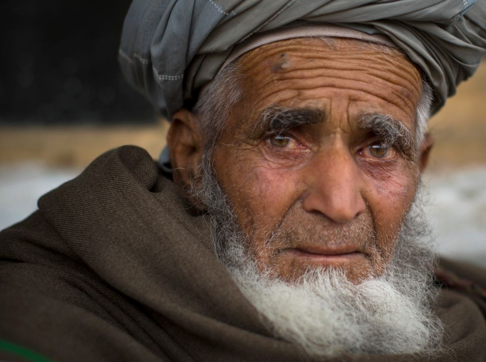 In this Wednesday, March 20, 2013 photo, Afghan villager Ghulam Rasool sits in the yard of his house where he and his family