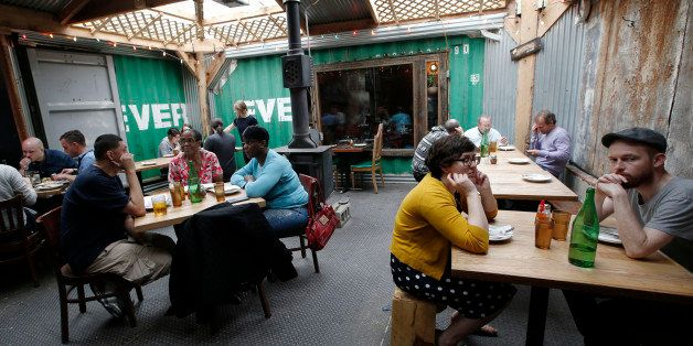 Patrons sit in an industrial-style courtyard where the walls are formed from pieces of metal shipping containers at Roberta's