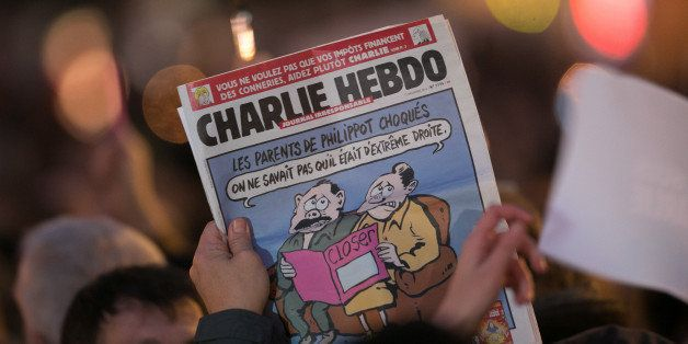 PARIS, FRANCE - JANUARY 07:  A person holds an issue of 'Charlie Hebdo' as crowds gather at 'Place de la Republique' during a