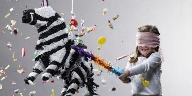 Young girl hitting pinata, candy flying
