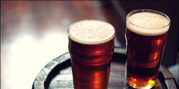 Two pints of beer bitter on wooden barrel in London pub.