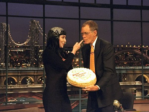 "Cher feeds cake to Dave for his birthday on ""The Late Show with David Letterman,"" April 12, 1999 on the CBS Television Networ"