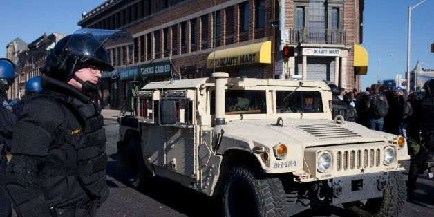A National Guard vehicle drives by a Maryland State Trooper Tuesday, April 28, 2015, in the aftermath of rioting following Mo