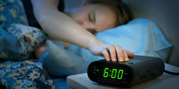 Canada, Ontario, Toronto, Teenage girl with hand on alarm clock