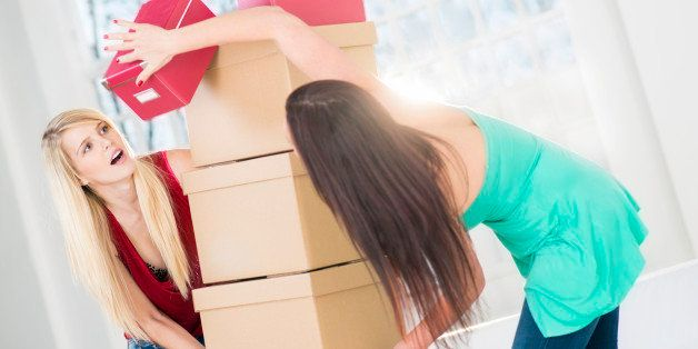 Female roommates moving into their dorm room.
