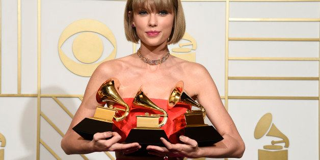Taylor Swift poses in the press room with the awards for album of the year for 1989, pop vocal album for 1989 and best music