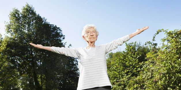 90 years old senior woman, making breathing exercise, with concentration outdoors at a wonder summer morning