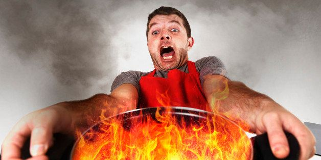 young inexperienced home cook with apron holding pot burning in flames with stress and panic face expression in fire in the k