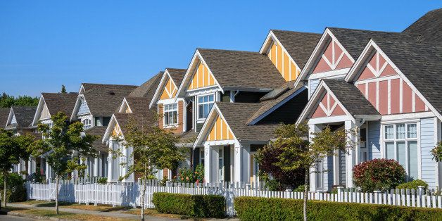 A row of a new houses in Richmond, British Columbia, Canada. Front yards of the houses and street with trees and bushes.