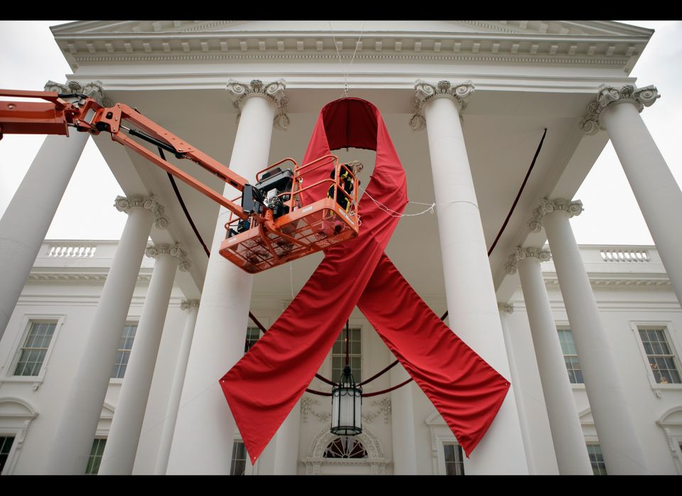 Workers hang a huge red ribbon on the North Portico of the White House one day ahead of World AIDS Day Nov. 30, 2011 in Washi