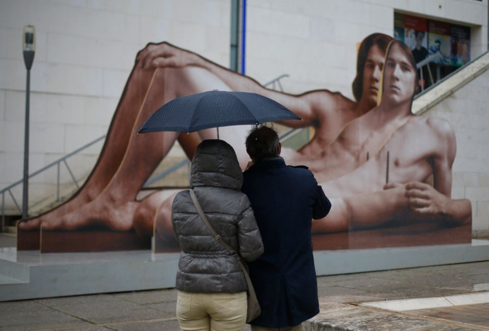 Tourists take a picture of an artwork entitled 'Mr Big' by Austrian artist Ilse Haider, displayed outside of the Leopold Muse
