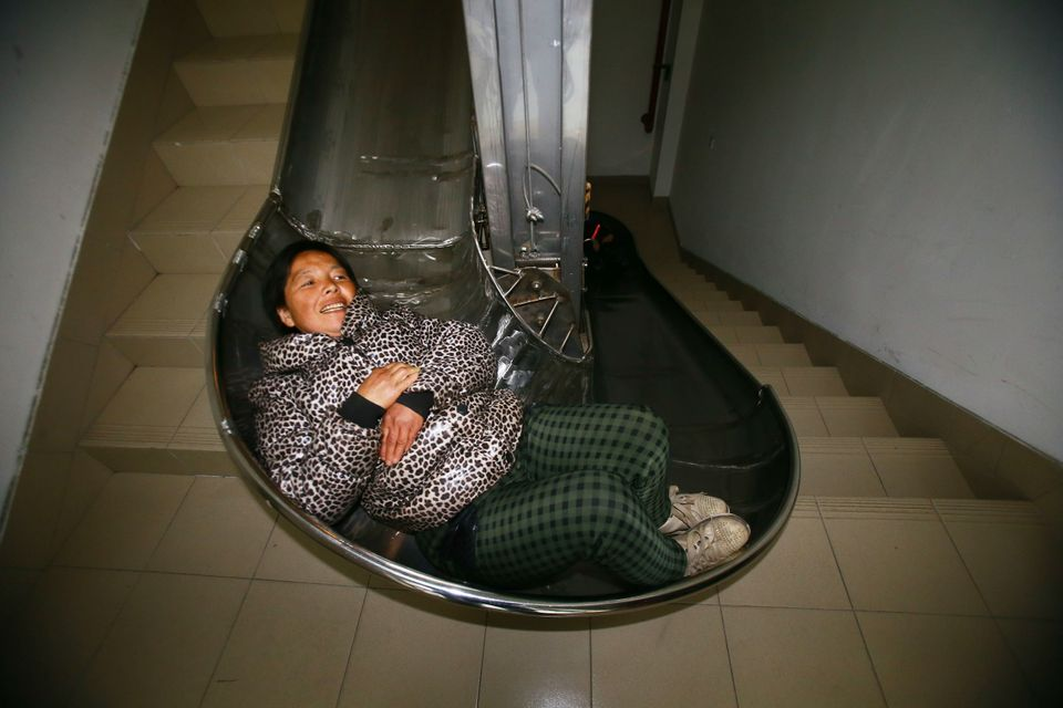 A woman tries out a newly invented emergency slide at the Service Center of Gumei Community, Minhang District, Shanghai, Chin