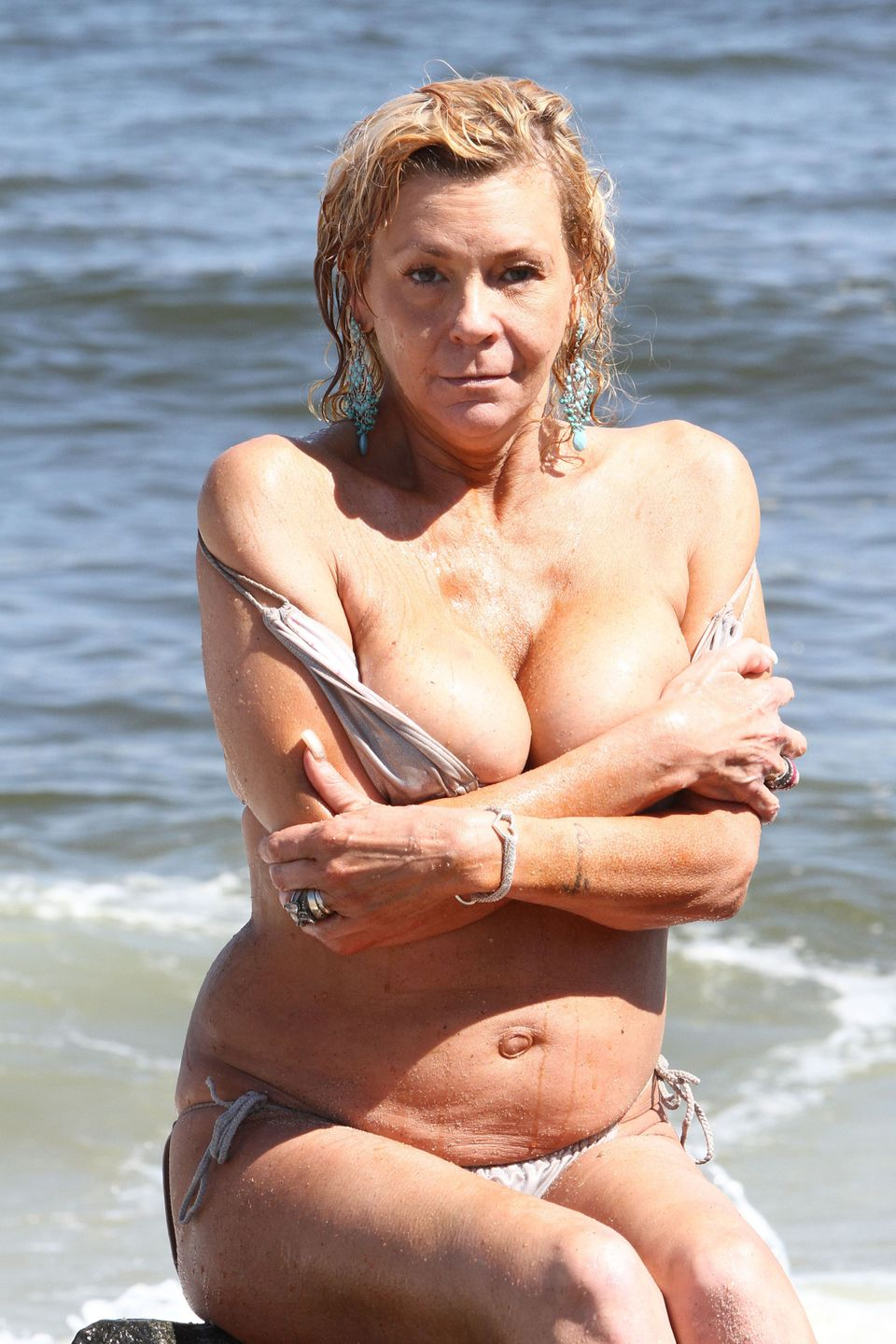 Tanning Mom, aka Patricia Krentcil, peels off her little silver bikini top while catching some sun on the beach in New Jersey