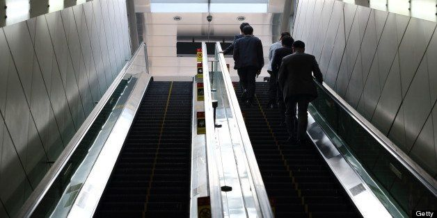 Morning commuters ride on an escalator at a subway station in Seoul, South Korea, on Monday, May 13,...