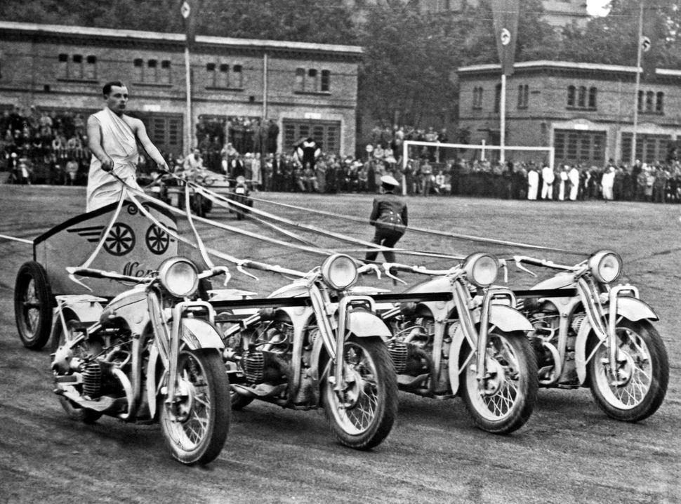A German Army soldier drives a 'team' of motorcycles from a chariot in a competition race at the Potsdam Army Show, Potsdam,