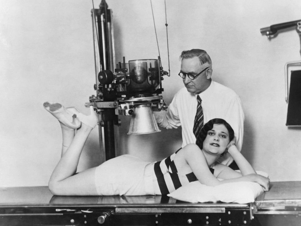 circa 1930: Ruth Hurschler, candidate to the 'Perfect Back' contest, is being examined and X rayed by Dr Howell, Chiropractor