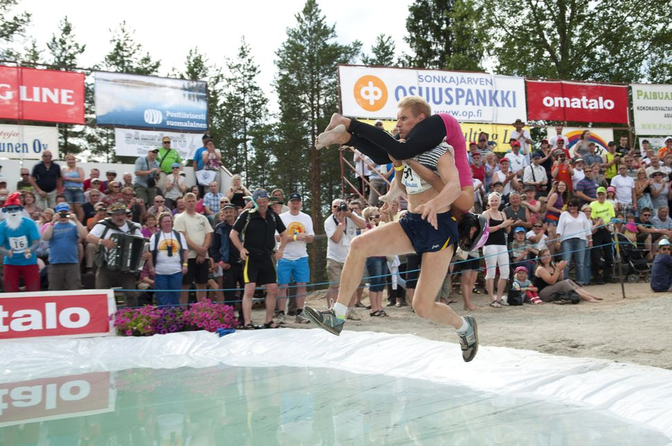 Taisto Miettinen carries his partner Kristiina Haapanen, during the Wife Carrying World Championship competition in Sonkajarv