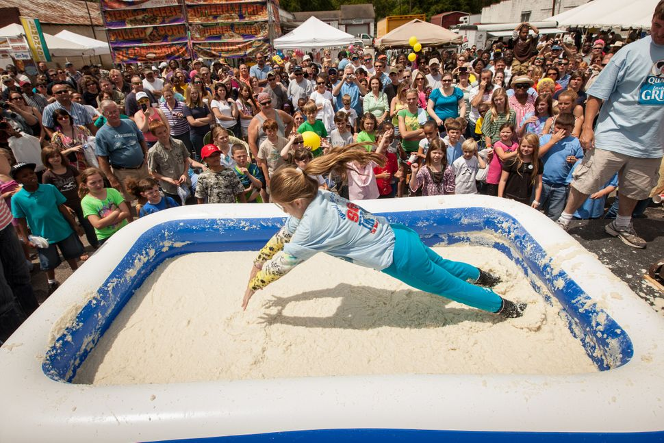 Kelsey, 12-years-old, dives into a pool of grits during the grits roll at the World Grits Festival on April 14, 2012 in St Ge