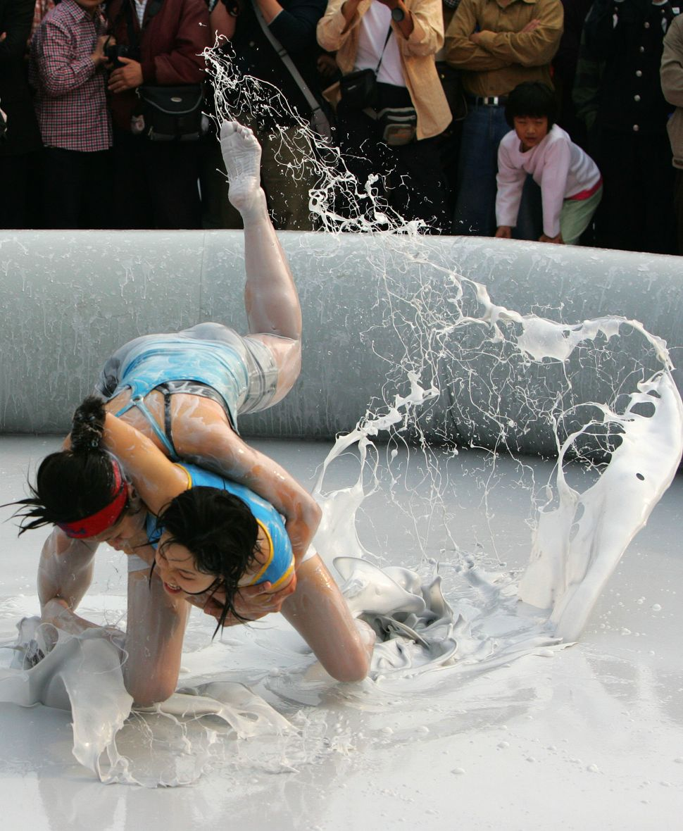 Two Chinese women wrestle in a mud pool during an international women's mud wrestling contest on March 28, 2010 in Haikou, Ha