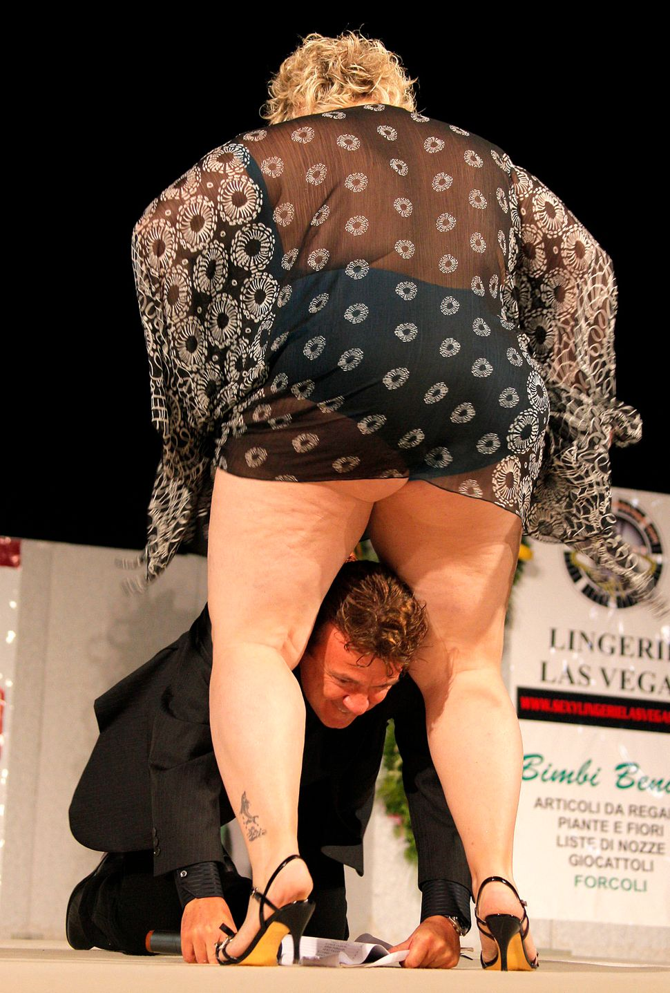 """A candidate of the 21st Italian national """"Miss Cicciona"""" (Miss Fat Woman) competition jokes with the host on the podium at Ca"""