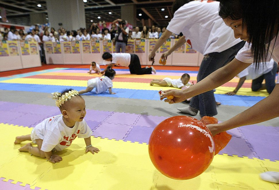 A mother (R) joins other parents in coaxing their babies toward the finish line in the 15th Hong Kong Baby Crawling Contest,