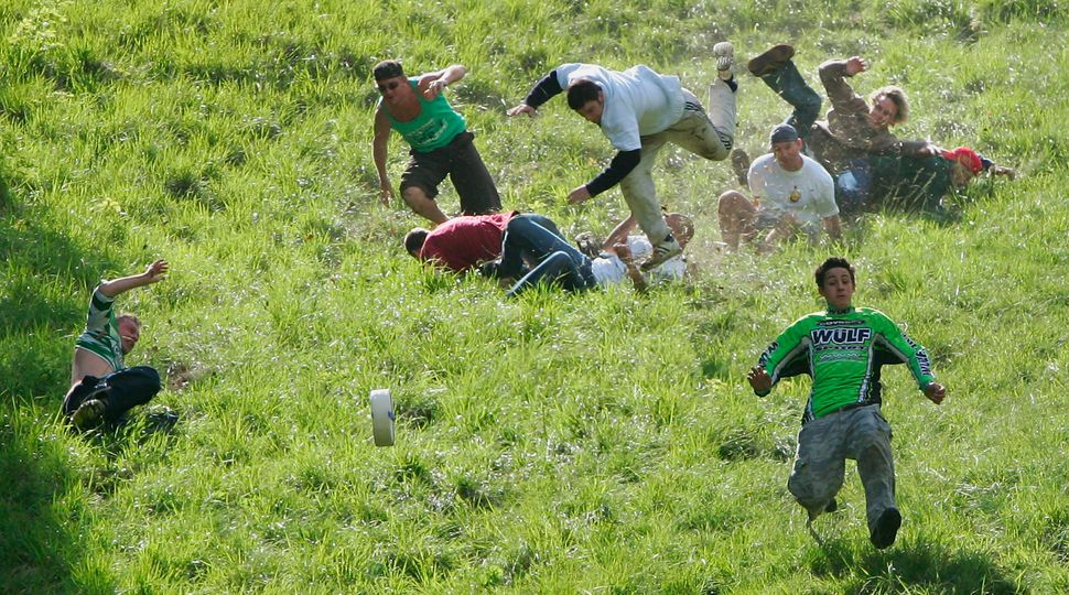 """Competitors hurl themselves down a near vertical slope in pursuit of a Double Gloucester cheese during the Gloucestershire """"C"""