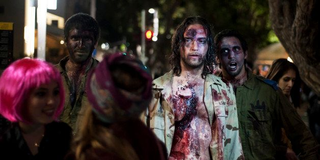 Israelis dressed as a zombies takes part in the customary 'Zombie Walk' in the city of Tel Aviv, on the eve of the Jewish hol