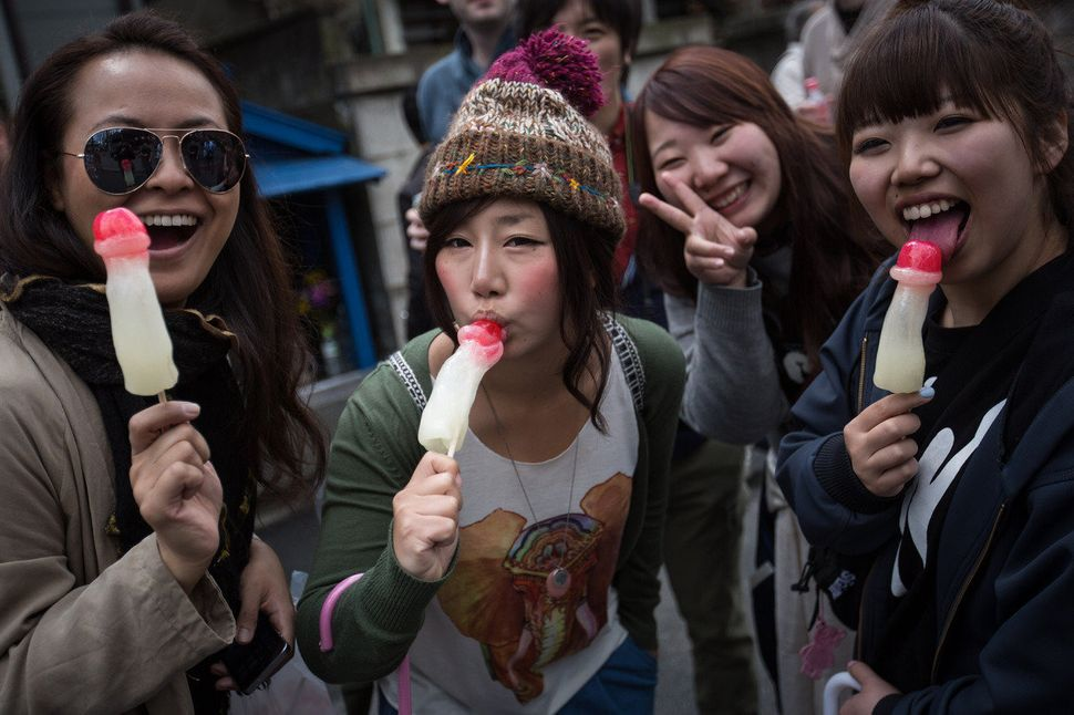 Women pose for a photograph as they munch on phallic-shaped lollipops.
