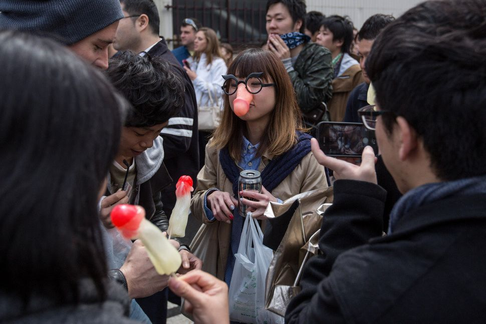 A woman wears a phallic-shaped mask as friends eat phallic-shaped lollipops at the Wakamiya Hachimangu shrine